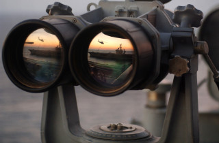 """051104-N-2984R-004 Onboard USS Harry S. Truman The sun sets over a set of """"Big Eyes"""" binoculars on the signal bridge of the Nimitz-class aircraft carrier USS Harry S. Truman (CVN 75), while an MH-60 Knighthawk assigned to the """"Bay Raiders"""" of Helicopter Combat Support Squadron (HSC) 28 airlifts several replenishment slings to USS Dwight D. Eisenhower (CVN 69).  USS Harry S. Truman is currently underway off the coast of the Eastern United States conducting replenishments at sea with USNS Arctic (T-AOE 8) and weapons offload operations with USS Enterprise (CVN 65) and USS Dwight D. Eisenhower (CVN 69). Harry S. Truman is scheduled to enter its Docked-Planned Incremental Availability at the beginning of 2006. US Navy photo by Photographer's Mate Airman Ricardo J. Reyes.  (Released by HST Public Affairs.)"""